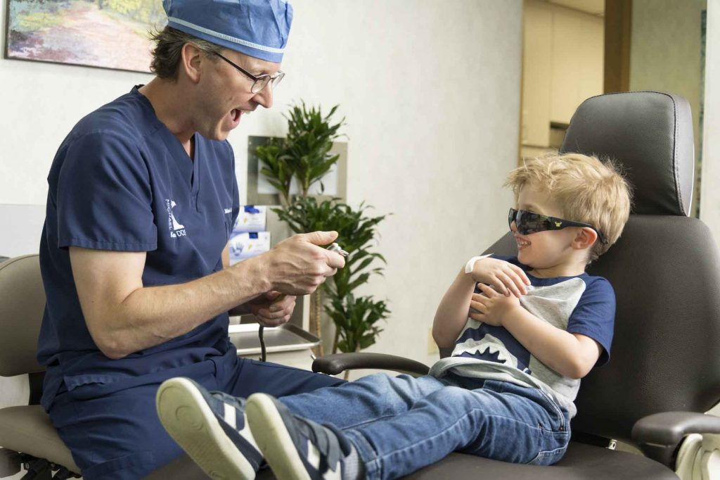 Dr. Michael Korn assists a pediatric dental patient who is sitting in an exam chair
