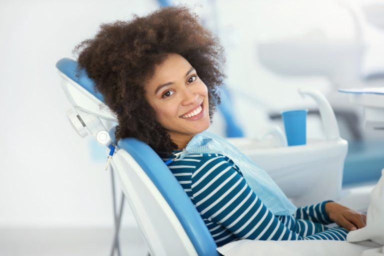 woman sitting in dental chair and smiling at the camera