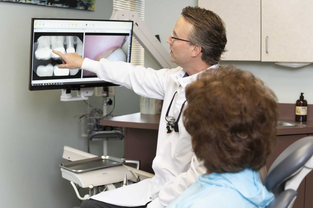 Dr. Michael Korn points to a dental x-ray while speaking to a dental patient